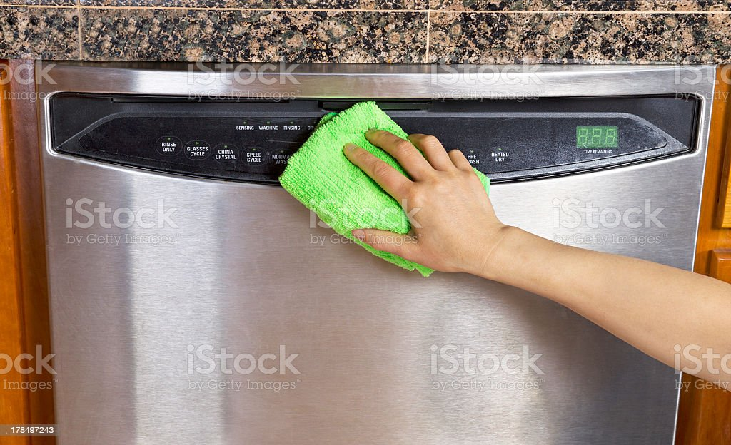 Wiping clean a silver dishwasher with a microfiber rag stock photo
