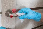 istock Wiping door knob with antibacterial disinfecting wipe for killing coronavirus. Coronavirus COVID-19 1216436476