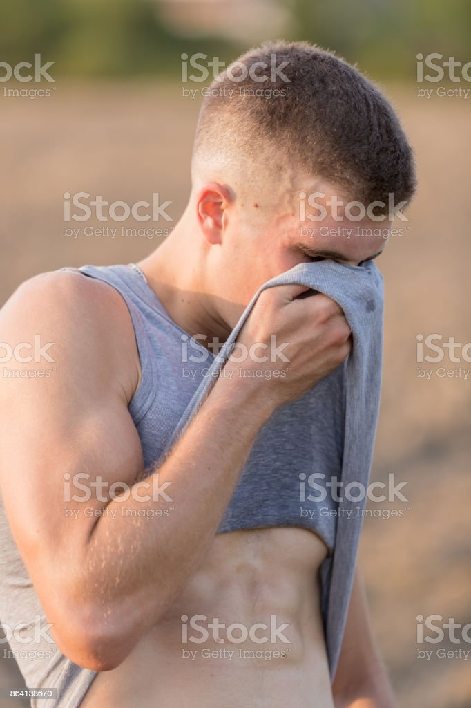 Wiping face with t-shirt royalty-free stock photo