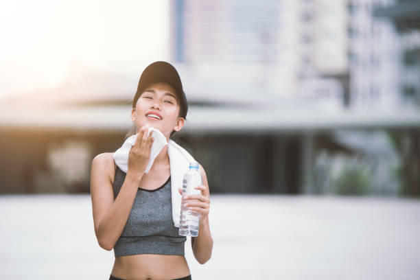 Wiping sweat Thirsty female jogger drinking fresh water after training. Young athletic woman exercising in the city park outdoors. stock photo