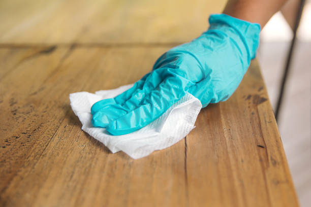 Wiping table surface regularly with disinfectant to kill virus stock photo
