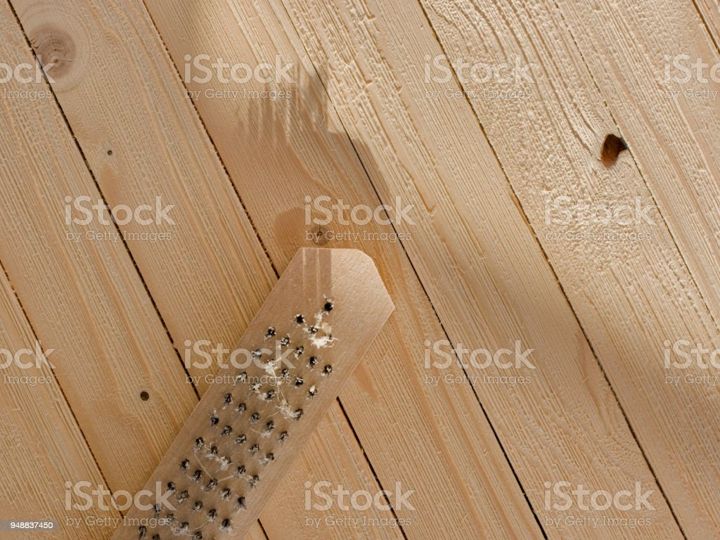 Wire brush and wooden surface. Artificially Aging and Weathering Wood. DIY: How to make new wood look old and weathered. stock photo