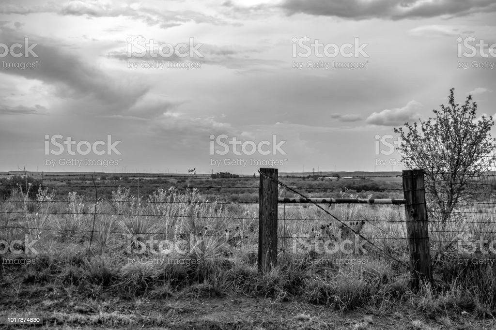 wire fence and post with sky Texas monochrome stock photo