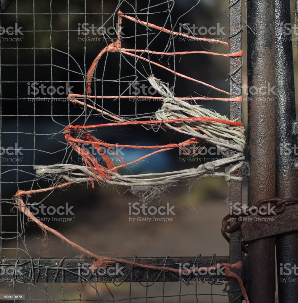 wire fence mended with string stock photo