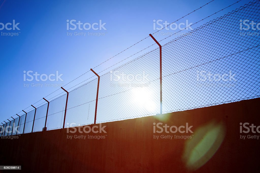 Wire fence with barbed wires stock photo