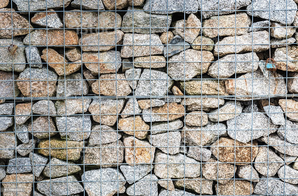 Wire Gabion Rock Fence. Metal Cage filled with rocks. stock photo