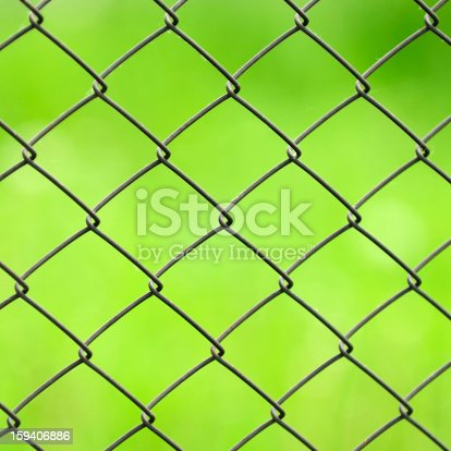 1176496357 istock photo Wire Mesh Fence Close-Up on Green Background 159406886