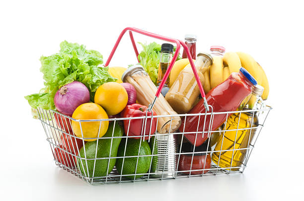 Wire shopping basket filled with groceries and vegetables A wire shopping basket filled with colorful groceries shot on white backdrop. Inside the basket are some fresh vegetables, fruits, canned food and cooking oil. Predominant colors are red, green and yellow. Visible soft shadow in the foreground.  shopping basket stock pictures, royalty-free photos & images