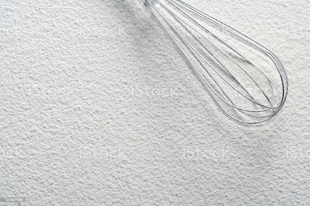 Wire whisk on flour stock photo