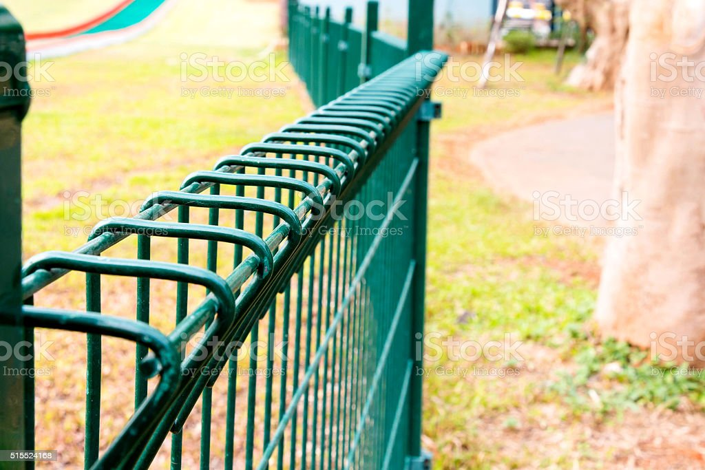 wired fence in park stock photo