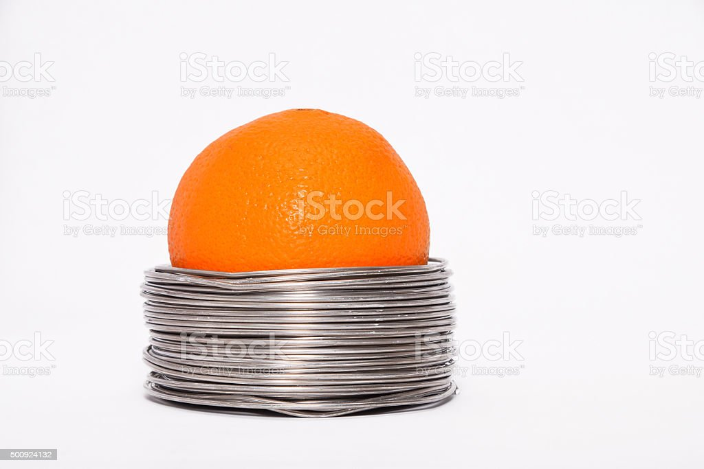 Wired orange: whole orange in coils of aluminium wire stock photo