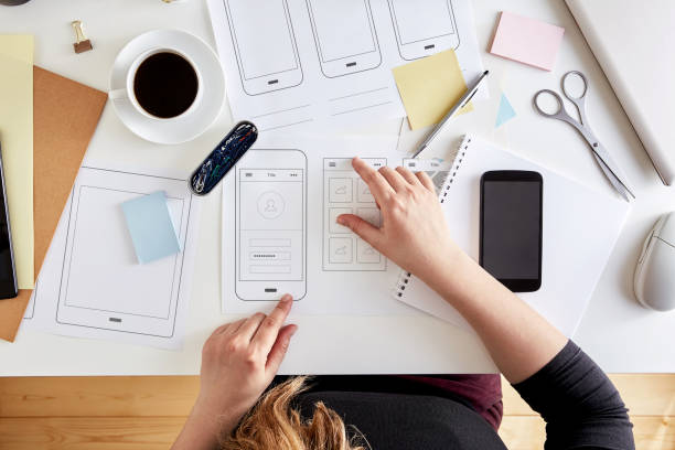 Wireframes. User experience concept Young UX graphic designer planning out the structure of a mobile application. Wireframing stage of a web mobile phone. Top view web design stock pictures, royalty-free photos & images
