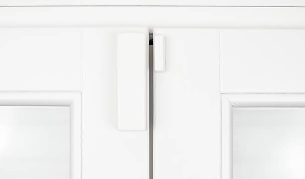 Wireless alarm sensor window door on white wooden sash Wireless battery magnetic alarm sensor for window and door on white wooden sash detail sensor stock pictures, royalty-free photos & images