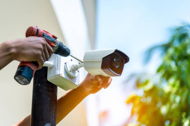 een draadloze cctv camera instelling buiten gebouw met witte doos water poof met zon vervagen achtergrond. - bewakingscamera stockfoto's en -beelden