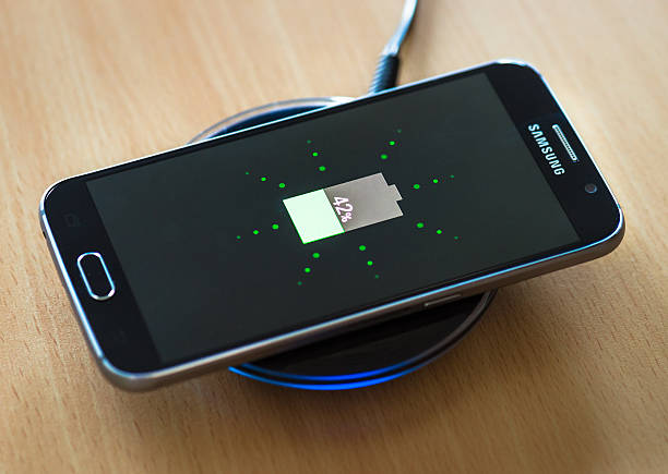 Wireless charging a Samsung Galaxy S6 smartphone Edinburgh, UK - April 20, 2015: A Samsung Galaxy S6 smart phone, charging on a Samsung wireless charging pad. battery charger stock pictures, royalty-free photos & images
