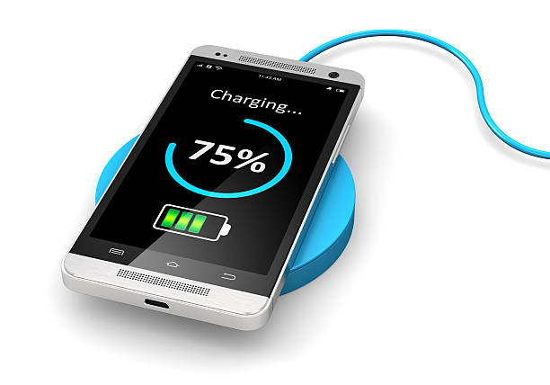 Wireless charging of smartphone Creative abstract modern communication technology business concept: wireless charging of modern black glossy metal touchscreen smartphone on wireless power charger battery charger stock pictures, royalty-free photos & images