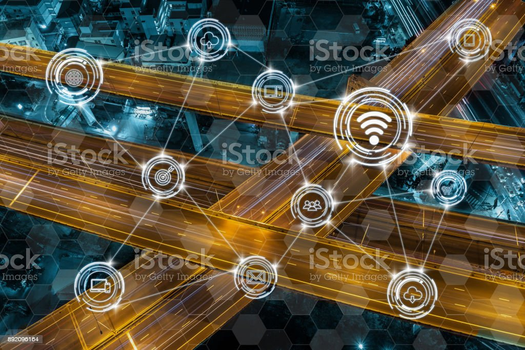 Wireless communication connecting of smart city Internet of Things Technology over Top view of massive expressway at night with light of cars, technology business IOT with transportation concept stock photo