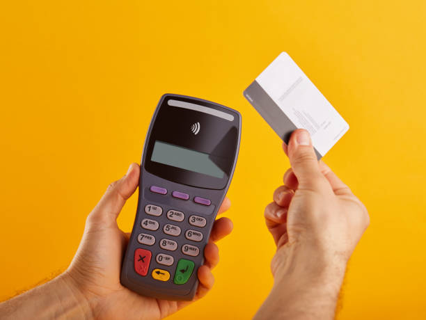 Wireless, contactless credit card reader. Electronic banking terminal and credit card in hand stock photo