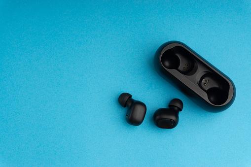 Wireless earbuds or earphones on blue background