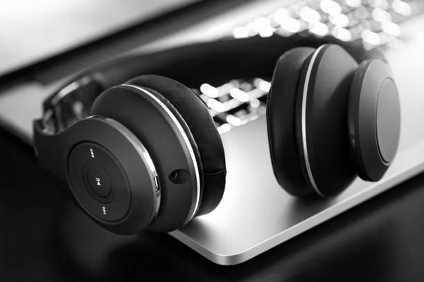 Wireless headphone on laptop Wireless headphone on laptop wireless headphones stock pictures, royalty-free photos & images