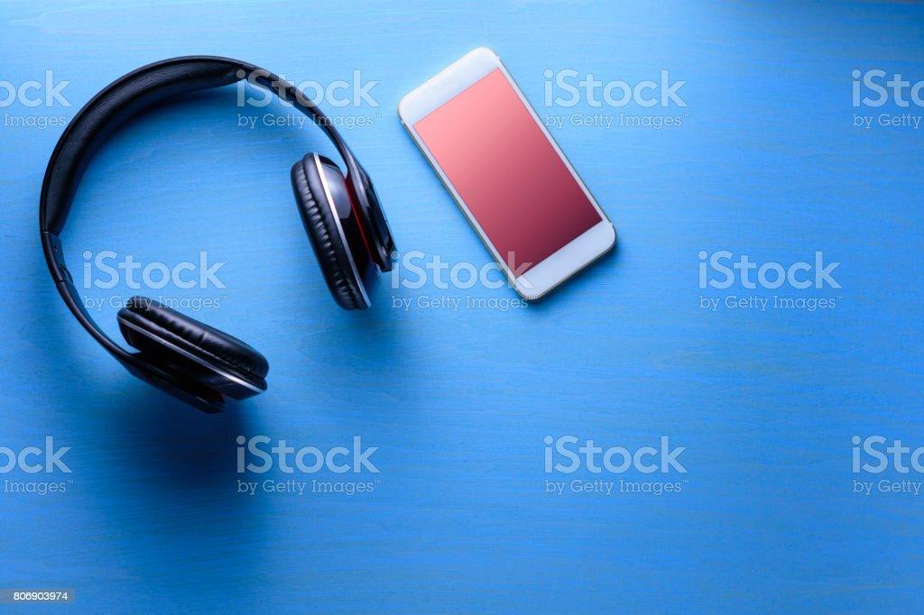 Auriculares inalámbricos con smartphone sobre fondo de madera azul - foto de stock