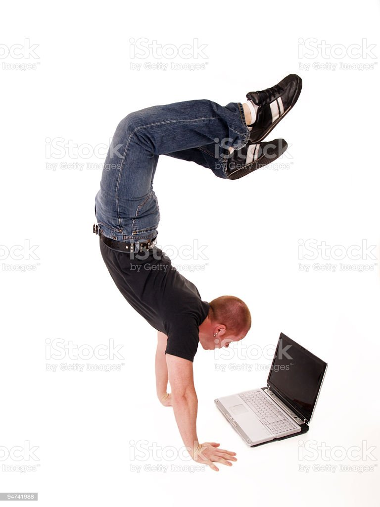 Wireless man on laptop doing a handstand in a black shirt royalty-free stock photo