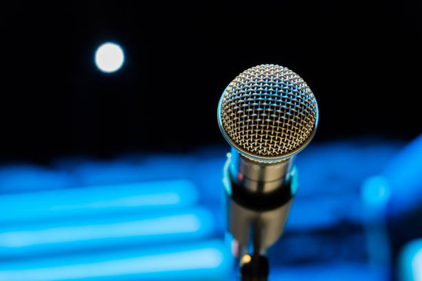 Wireless microphone on stand on blurred background. Empty audience