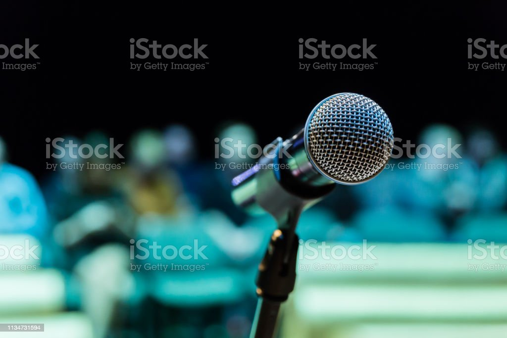 Wireless microphone on the stand. Blurred background. People in the...