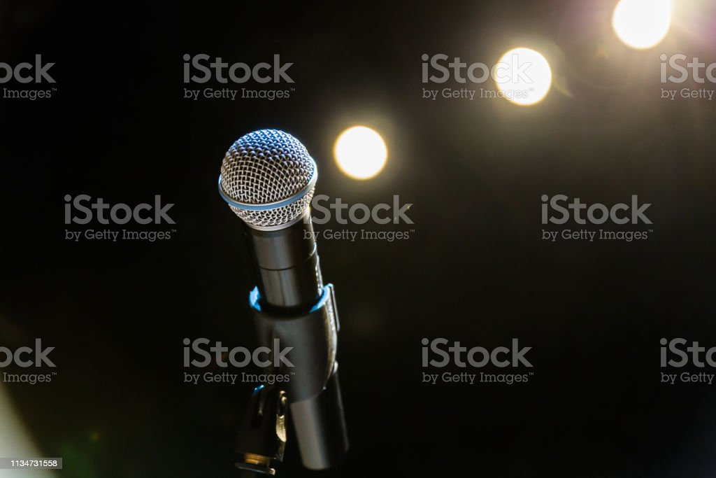 Wireless microphone on the stand on the background of spotlights on...