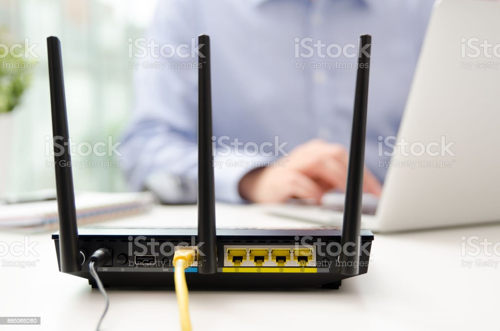 Wireless router and man using a laptop in office – zdjęcie
