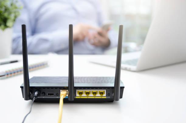 wireless-router und mann mit einem smartphone in haus - router stock-fotos und bilder