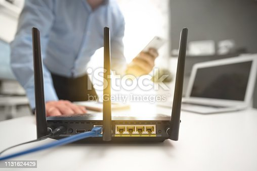 Wireless router with three antennas and cable connected. Man using smartphone in background