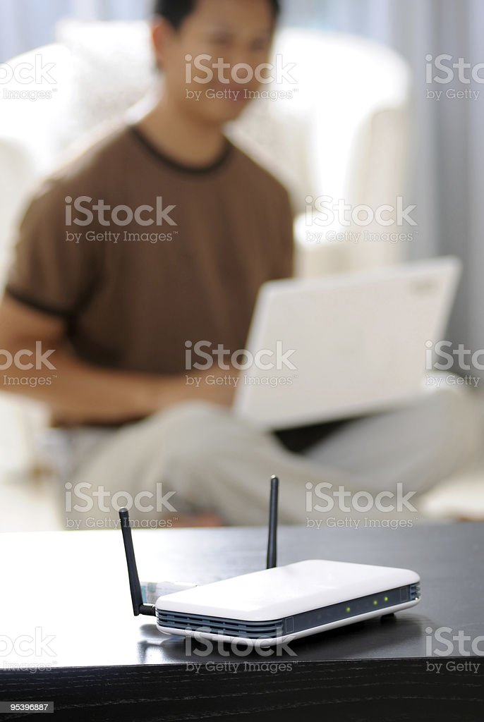 A wireless router in the foreground of a man on a laptop stock photo