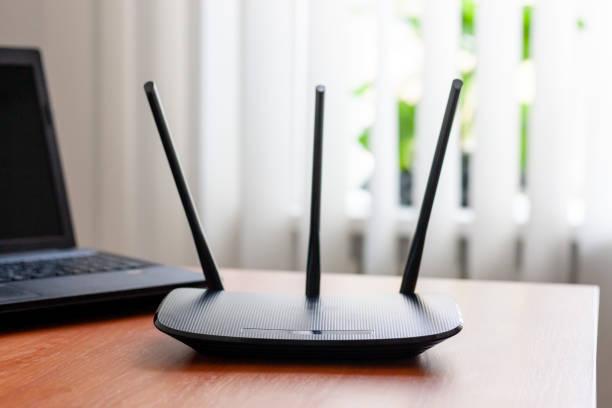 wisch-fiobrouter und laptop an holztisch drinnen. fenster dahinter. wlan-verbindungskonzept. - router stock-fotos und bilder