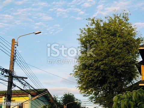 Electrical Wires, Telephone Line and Street Light on The Pole Against Blue Sky.