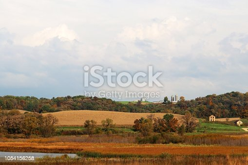 Autumn rural landscape with farms scattered among forested hills and fields and cloudy sky over. Typical Wisconsin countryside view, Midwest USA.