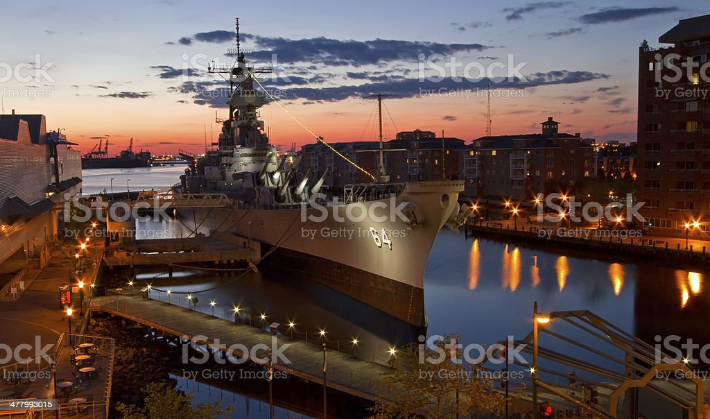 USS Wisconsin Battleship (BB-64) in Norfolk, Virginia, at sunset Overhead view of the battleship USS Wisconsin at twilight, the ship was decomissioned in 1991, and is currently docked in Norfolk, Virginia. Armed Forces Stock Photo