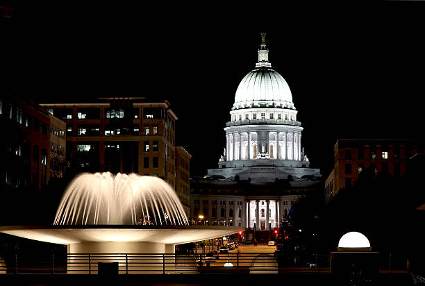 Wisconsin State Capitol building National Historic Landmark. Madison, Wisconsin, USA. Night scene with official buildings and illuminated fountain on the foreground. View from Monona terrace balcony, horizontal composition. wisconsin state capitol stock pictures, royalty-free photos & images