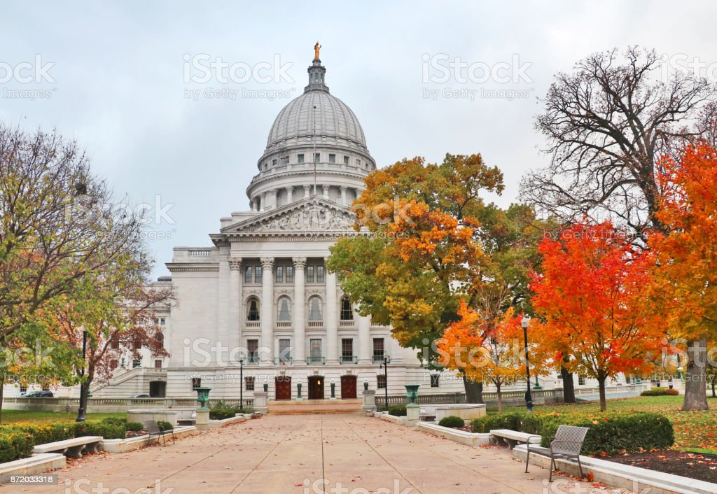 Wisconsin State Capitol building National Historic Landmark city of Madison, Wisconsin, Midwest USA. Autumn view with bright colored trees along path to the entrance and cloudy sky during later afternoon. Architectural Column Stock Photo