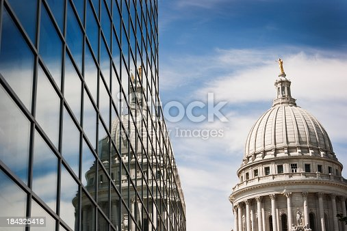 Horizontal view of the Wisconsin State Capitol Dome reflecting into the windows of a steel and glass office building on a sunny day.