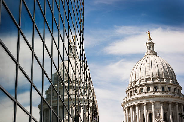 Wisconsin State Capitol Dome Reflecting in Steel and Glass Building Horizontal view of the Wisconsin State Capitol Dome reflecting into the windows of a steel and glass office building on a sunny day. madison wisconsin stock pictures, royalty-free photos & images