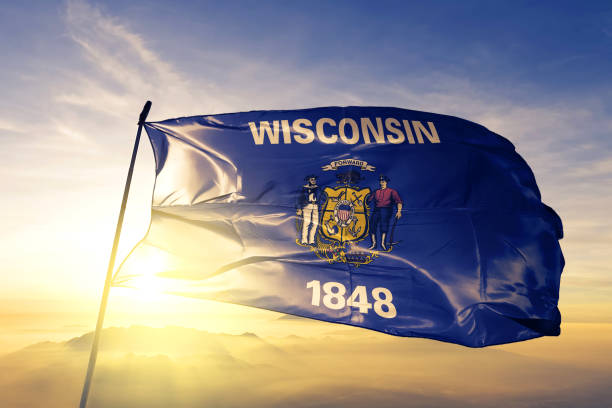 Wisconsin state of United States flag textile cloth fabric waving on the top sunrise mist fog Wisconsin state of United States flag on flagpole textile cloth fabric waving on the top sunrise mist fog wisconsin stock pictures, royalty-free photos & images