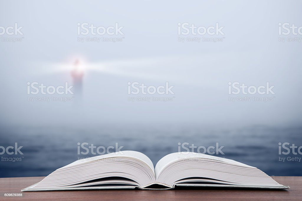 Wisdom concept open book over sea and lighthouse stock photo