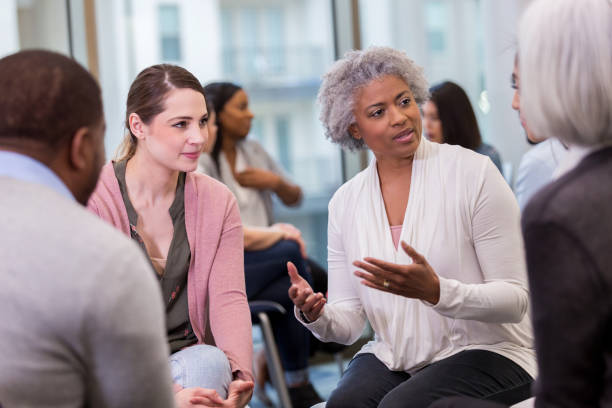 A wise mature woman shares with coworkers During the breakout session at the conference, a mature woman share insights she has gained in the workplace. group therapy stock pictures, royalty-free photos & images