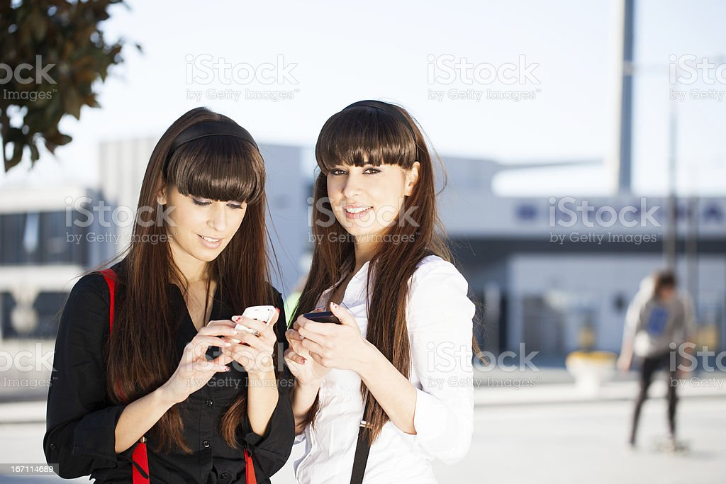 Wise Sisters Using Smart Phones royalty-free stock photo