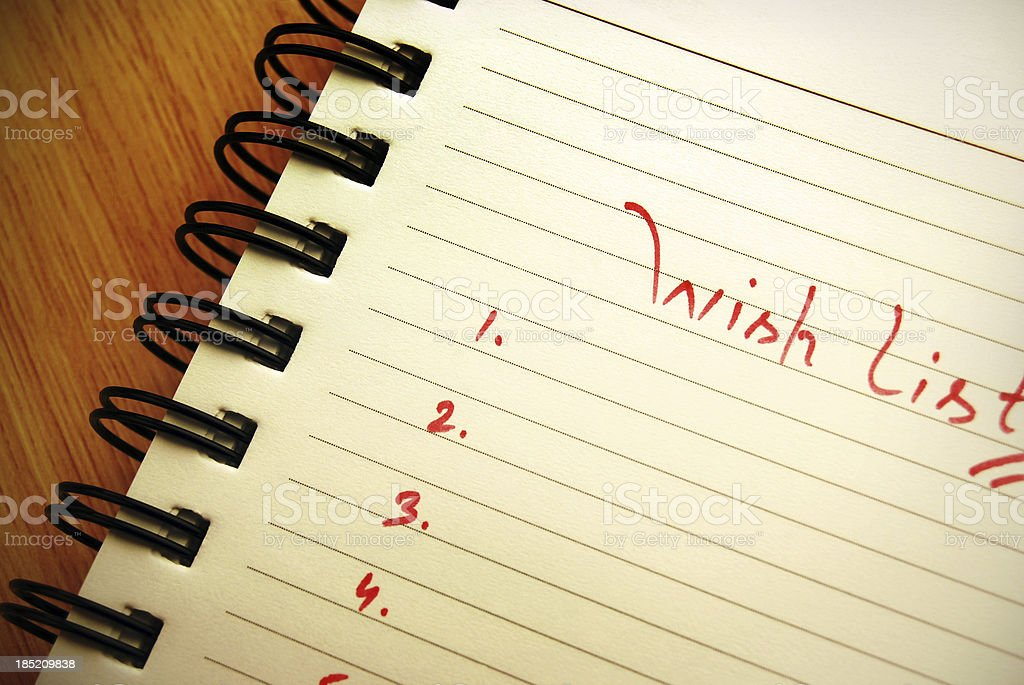 \'Wish list\' written on a spiral pad. Focus on and around centre of...