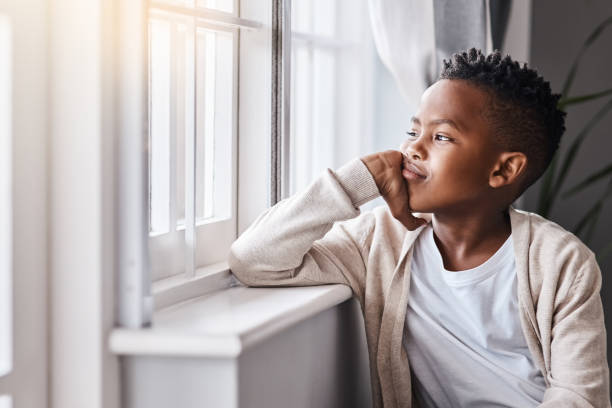Wish there was something fun for me to do Shot of an adorable little boy looking out the window at home boy looking out window stock pictures, royalty-free photos & images