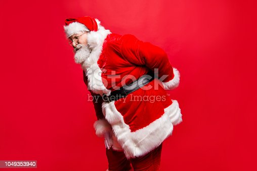 istock I wish visit chiropractor! Profile side view stylish aged unhealthy spine mature Santa in costume headwear gloves with scoliosis pose with cramp spasm or injury in back isolated noel red background 1049353940