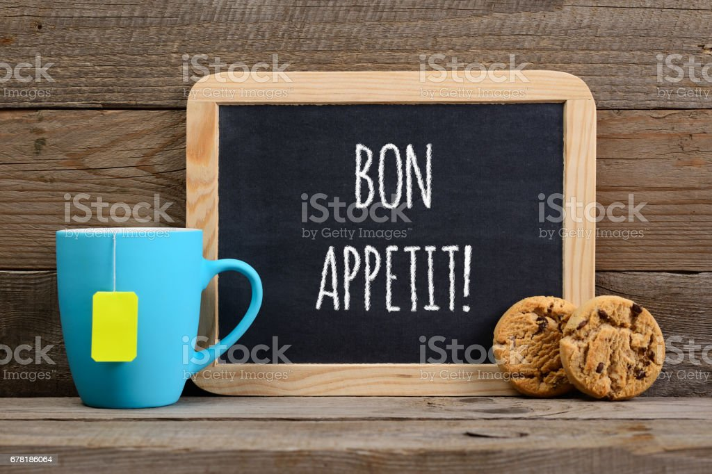 Wishes bon appetit on small blackboard, cup of tea and cookies stock photo