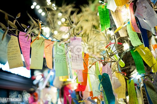 Wishes written on Tanzaku, small pieces of paper, and hung on a Japanese wishing tree, located in the Little Tokyo section of Los Angeles, California, photographed at an outdoor mall at night.